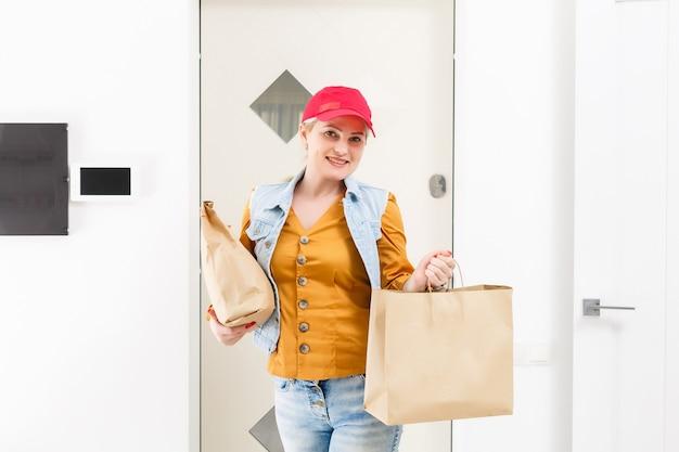 Mujer en gorra roja dando fondo de casa de orden de comida rápida. mensajero de sexo femenino que sostiene el paquete de papel con la comida. entrega de productos desde tienda o restaurante a domicilio. copia espacio