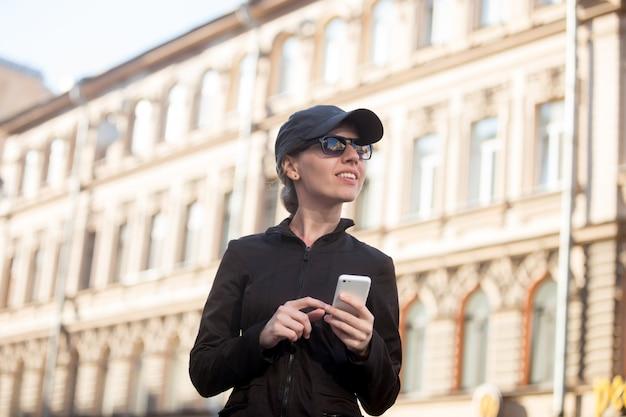 Mujer con gorra usando su teléfono