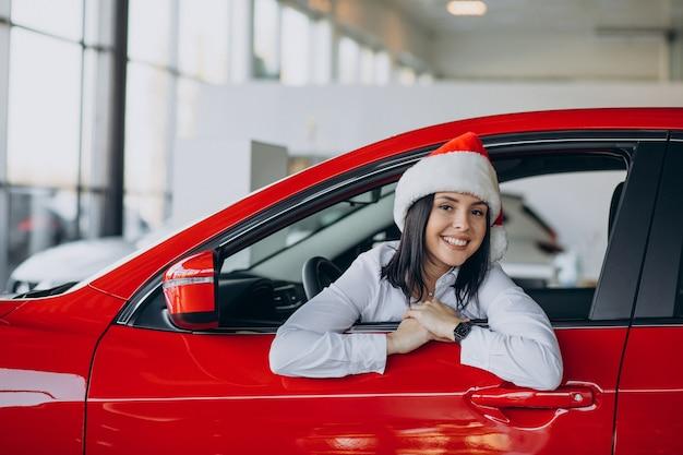Mujer con gorro de papá noel por el coche rojo en una sala de exposición de coches