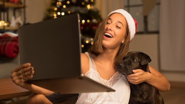 Mujer con gorro de papá noel mostrando su perro a personas de guardia usando laptop