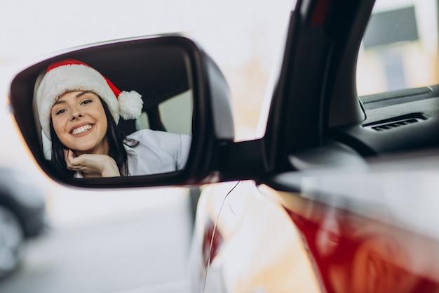 Mujer con gorro de papá noel en navidad en la sala de exposición de automóviles