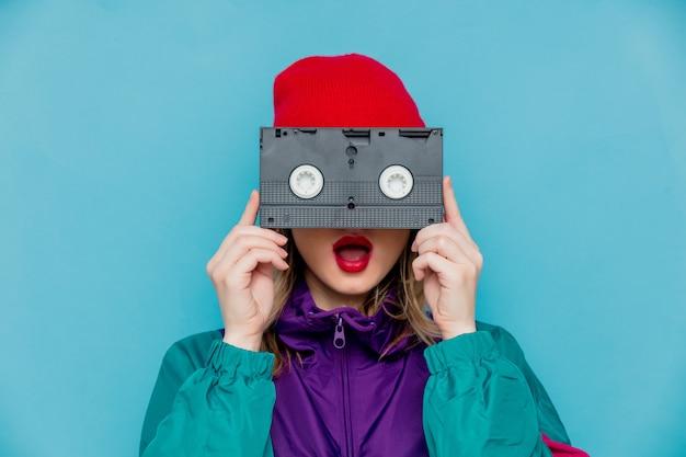 Mujer con gorro rojo, gafas de sol y traje de los años 90 con cassette vhs.