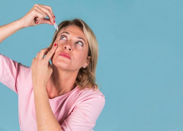 Mujer goteando gotas médicas en sus ojos