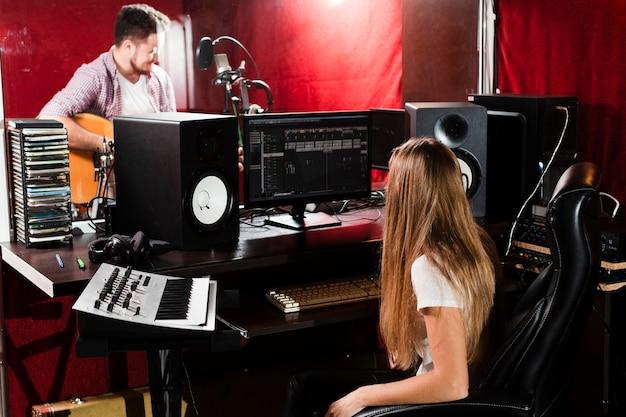 Mujer graba guitarra y chico tocando en el estudio
