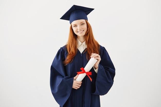 Mujer graduada de jengibre feliz en gorra y manto sonriendo sosteniendo diploma.