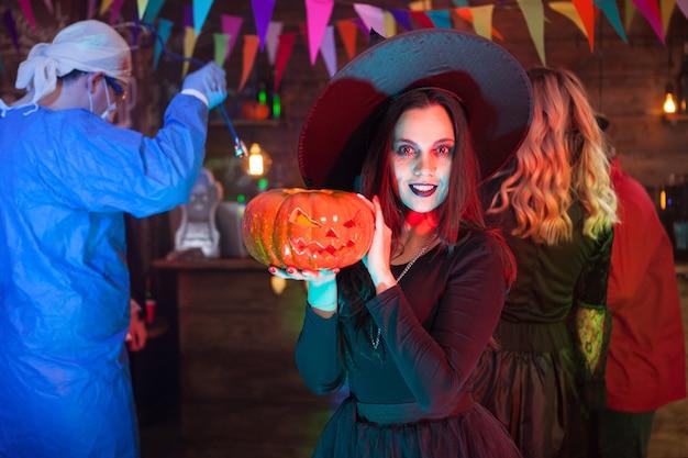Mujer con una gran sonrisa vestida como una bruja para la celebración de halloween. chica sosteniendo una calabaza.
