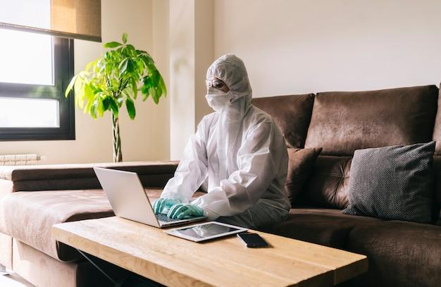 Una mujer con grandes medidas de seguridad contra un virus trabaja desde casa