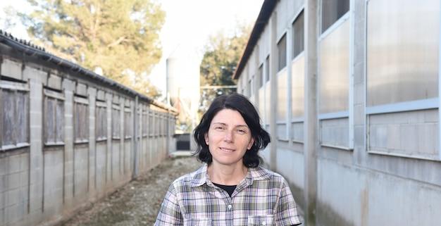 Mujer de granja frente a una granja de animales