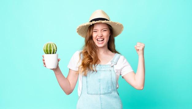 Mujer de granjero bonita cabeza roja gritando agresivamente con una expresión de enojo y sosteniendo un cactus