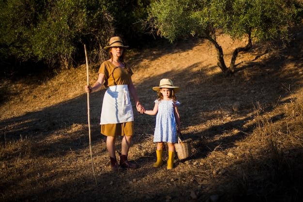 Mujer del granjero que lleva a cabo la mano de su hija que se coloca en el campo