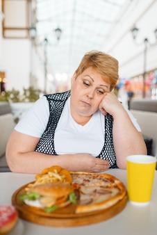 Mujer grasa comiendo pizza en restaurante de comida rápida