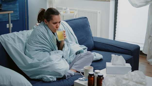Mujer con gripe bebiendo medicación efervescente con agua