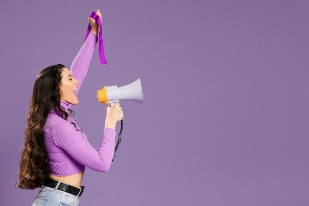 Mujer gritando en megáfono de pie de lado con espacio de copia