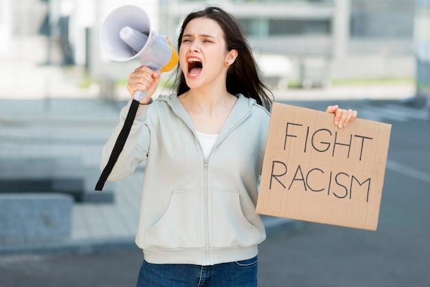Mujer gritando en megáfono y sosteniendo cartón