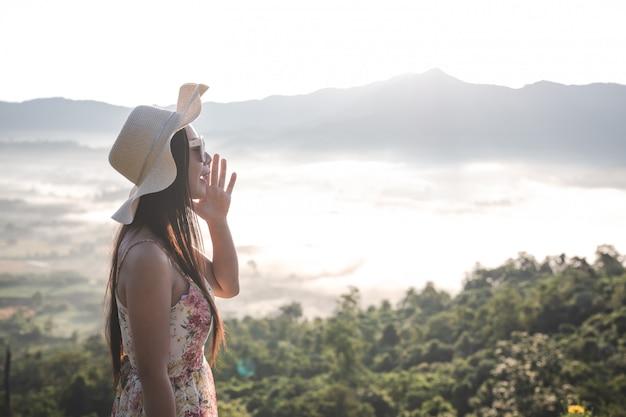 Una mujer gritando en las montañas