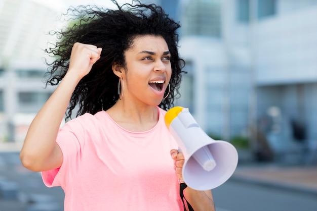 Mujer gritando en vista lateral de megáfono