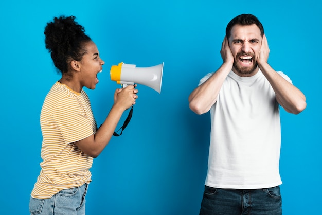 Mujer gritándole al hombre a través del megáfono