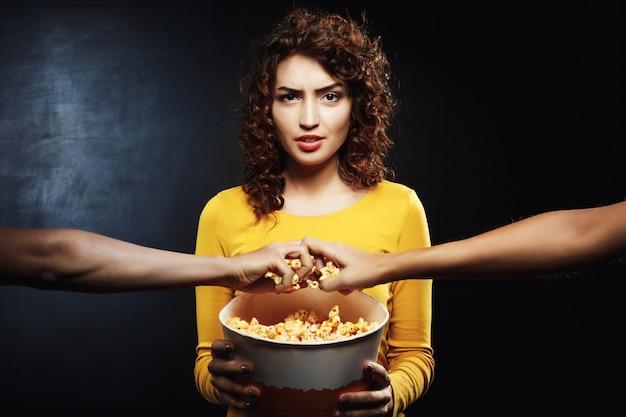Mujer gruñona que sostiene un cubo de palomitas de maíz y no quiere compartir