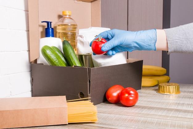 Una mujer con un guante de goma endulza un tomate rojo en una caja con productos para donación