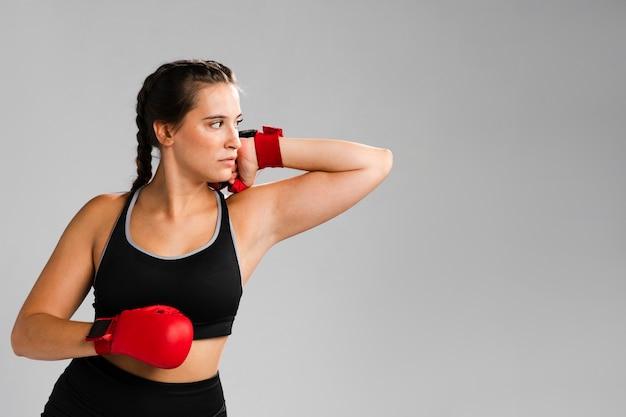 Mujer con guantes de box mirando a otro lado y copiar el fondo del espacio