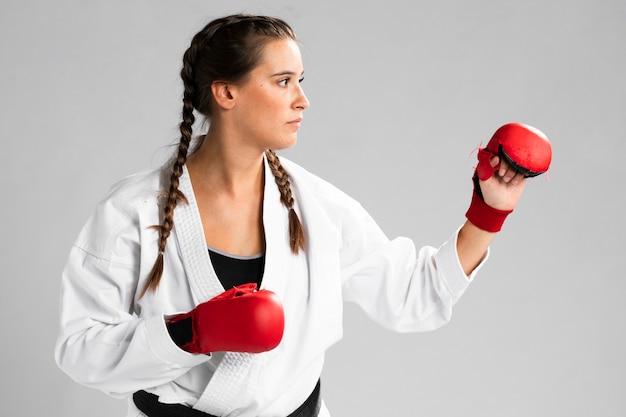 Mujer con guantes de box sobre fondo blanco.