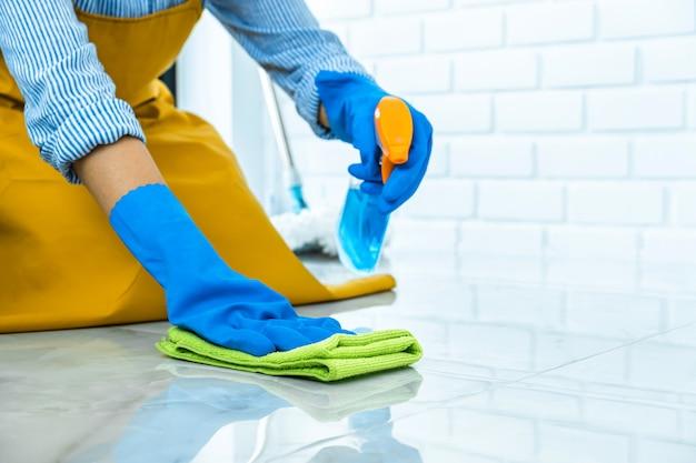 Mujer con guantes de goma azul limpiando el polvo con un spray y un plumero mientras limpia en el piso