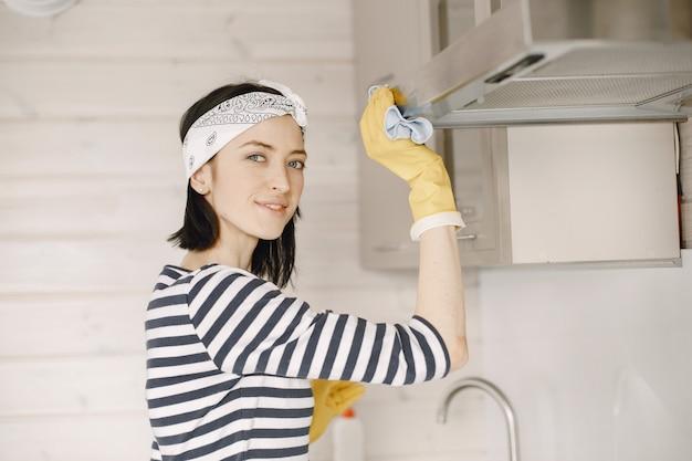Mujer con guantes de goma limpiando la cocina.