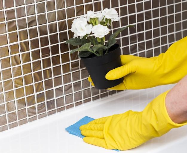 Mujer con guantes de goma limpiando el fregadero