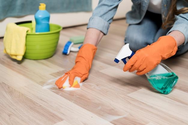 Mujer con guantes de goma limpiando los pisos