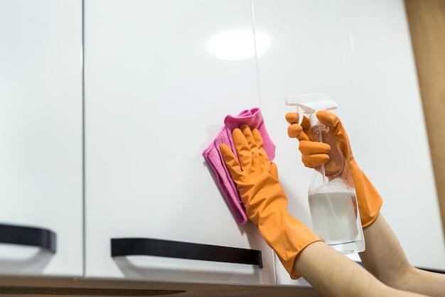 Mujer con guantes de goma limpiando la superficie sucia en la cocina. tareas del hogar
