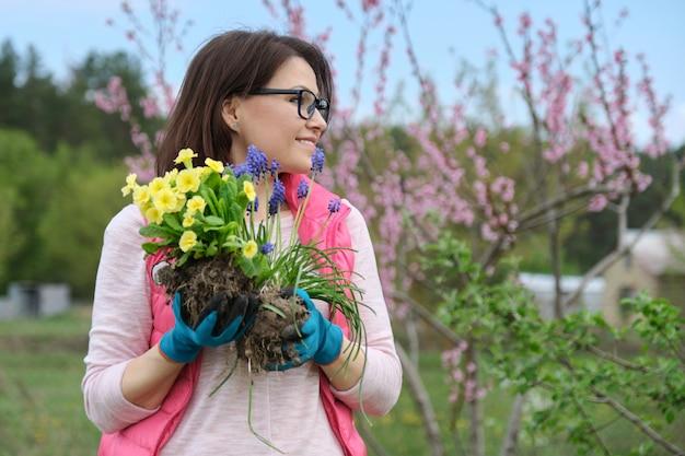Mujer en guantes de jardín con flores para plantar