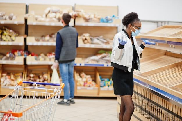 Mujer con guantes y máscara médica desechable de compras en el supermercado durante el brote de pandemia de coronavirus.