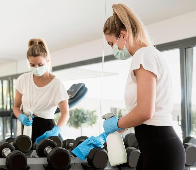 Mujer con guantes y mascarilla médica desinfectando pesas en el gimnasio