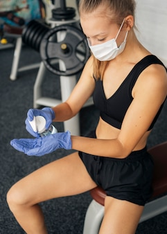 Mujer con guantes y mascarilla médica en el gimnasio con desinfectante de manos