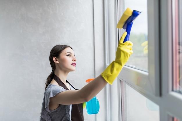 Mujer con guantes de protección está sonriendo y limpiando el polvo con un spray y un plumero mientras limpia su casa, primer plano