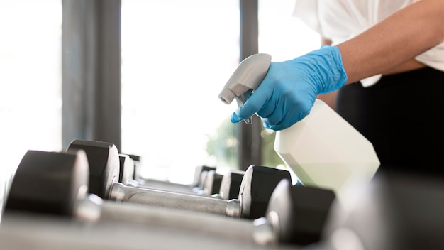 Mujer con guantes y solución de limpieza desinfectante de pesas de gimnasio