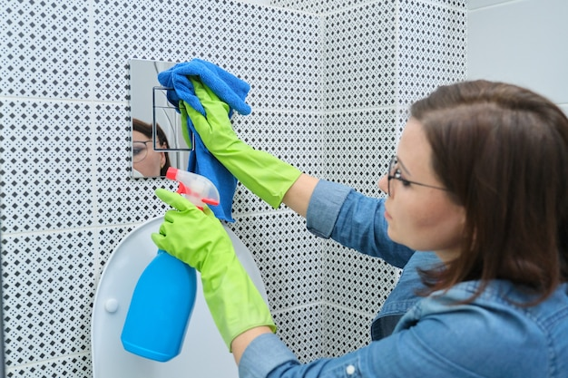 Mujer en guantes con trapo haciendo limpieza en el baño.
