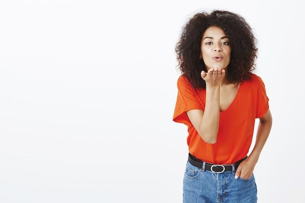 Mujer guapa saliente con peinado afro posando en el estudio