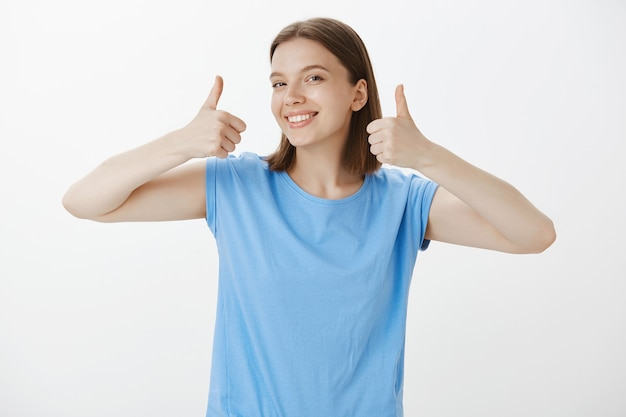 Mujer guapa satisfecha sonriendo y mostrando el pulgar hacia arriba en señal de aprobación, garantía de calidad
