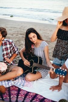 Mujer con guitarra en la playa