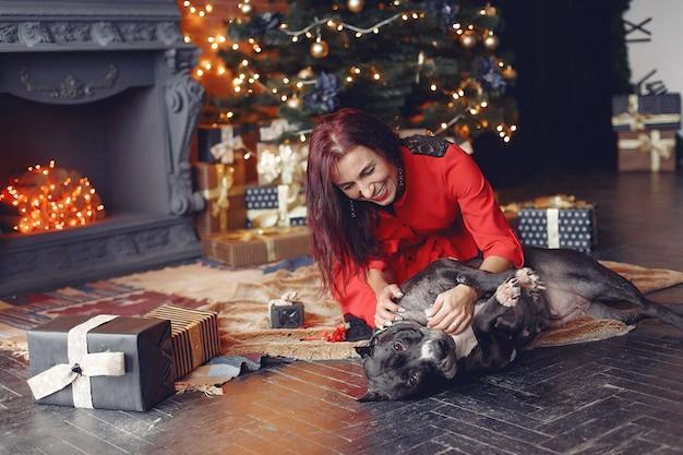 Mujer en una habitación. morena con un vestido rojo. señora cerca del árbol de navidad.