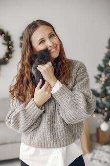 Mujer en una habitación. persona con un suéter gris. señora con gatito.