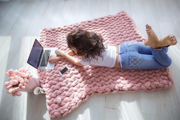Una mujer en una habitación en el piso cerca de su computadora portátil.