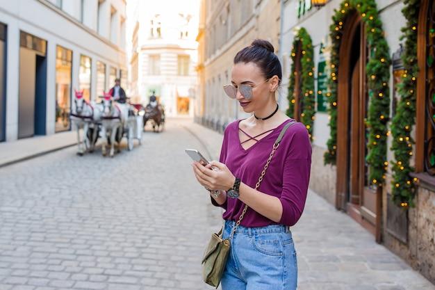 Mujer habla por su teléfono inteligente en la ciudad. joven turista atractivo al aire libre en ciudad italiana
