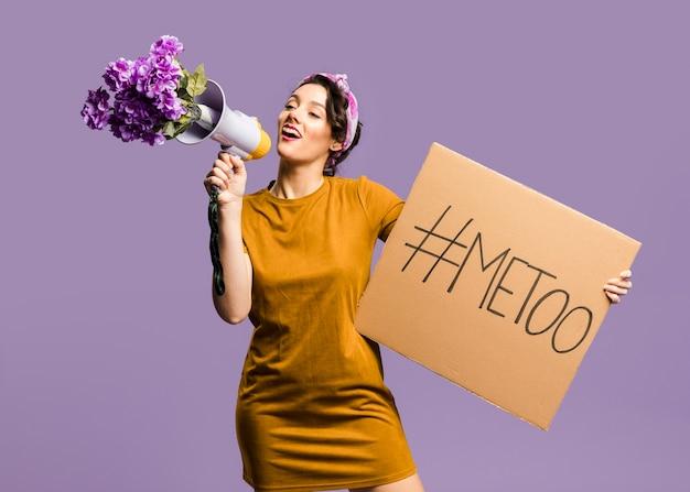 Mujer hablando por megáfono y sosteniendo cartón con cartel