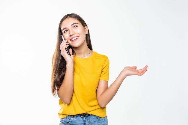 Mujer hablando por su teléfono celular sobre una pared blanca