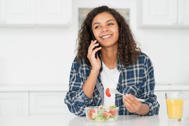 Mujer hablando por teléfono y comiendo ensalada