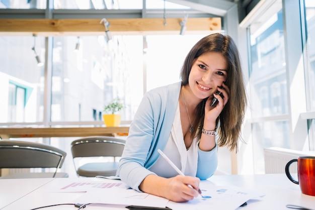 Mujer hablando por teléfono y corrigiendo gráficos