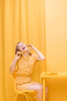 Mujer hablando por teléfono en escenario amarillo
