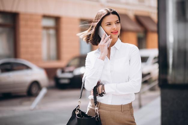 Mujer hablando por teléfono fuera de las calles de la ciudad